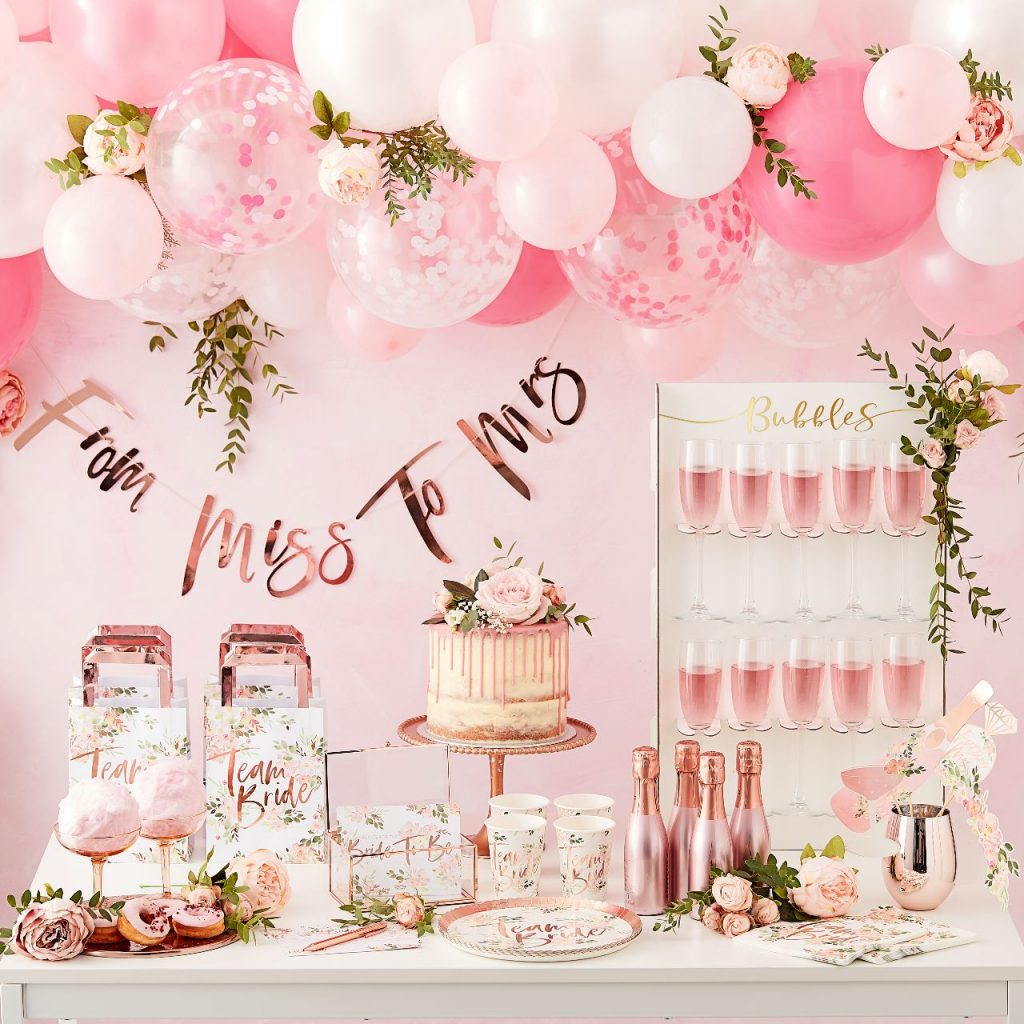 A floral themed hen party table with balloons, decorations, cake and drinks