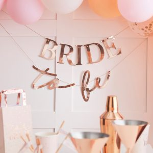 A rose gold bunting sign on the wall saying bride to be