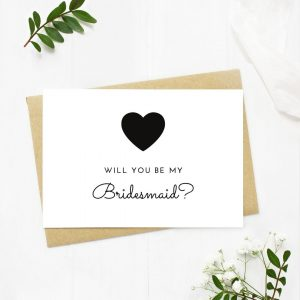 A white card saying will you be my bridesmaid with a heart symbol on it